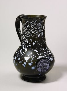 Jug; glass; greenish; pear-shaped; small lip; ornamented with white dots and splashes; plain handle; inscribed bottle seal.