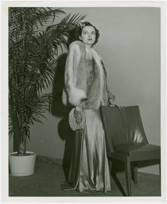 Fashion, World of - Models - Coats - Model with hand on chair From New York Public Library Digital Collections.