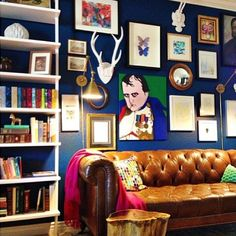 Navy walls - Chesterfield Sofa - Book Shelves - love the hot pink throw.