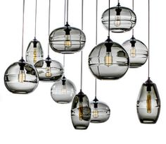 """Hand-blown glass pendants with thick clear band optic lens. Canopies may be either circular, rectangular or square, and are available in a range of metal finishes including; oil rubbed blackened steel (standard), polished chrome, satin chrome, satin brass, satin nickel, antique brass, polished nickel, polished brass, and oil rubbed bronze.  Available in three different shapes:  Shade dimension: • Wide: aprx 11"""" x 8"""" • Sphere: aprx 10.5"""" x 10"""" • Long: 6.5"""" x 12""""  Discount to members of the…"""