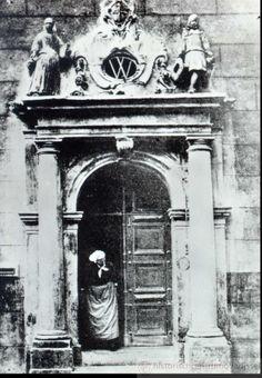 """Oude vrouw in Zwolse klederdracht in de poort van het Weeshuis in de Broerenstraat 11, ca. 1900. Vroeger stond hier het St. Caeciliaklooster, in de volksmond het convent `ter Kinderhuis"""" genoemd, omdat de nonnen de kinderen plachten te onderwijzen. Na de Hervorming werd van het grootste gedeelte van het uit 1417 daterende gebouw een weeshuis gemaakt voor de zogenaamde vreemde wezen.     #Overijssel #Salland"""