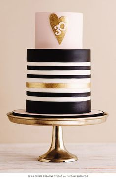 A pink and gold 30th birthday cake table featuring black and white stripes, gold glittering hearts and sparkling details.