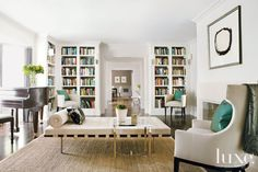 Bookshelves encircle this contemporary library adding a sophisticated flare while tailored tub chairs, covered with Classic Cloth fabric from Kneedler-Fauchère add classic glamour.