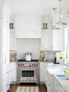 A small, narrow space always looks bigger and more open when painted white. Here, the dark wood floor topped in white all the way to the ceiling keeps the eye moving up. Lots of long vertical and horizontal lines -- in the rug, on the cabinetry, along the subway tile and on the ceiling -- is another visual room-extending trick. /