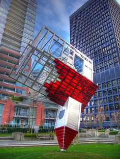 """The designer of the bus stop is Dennis Oppenheim, a pioneering artist in conceptualism, land art, body art, video, and sculpture since the 1960s. In 1997, he created the sculpture shown below called """"Device to Root out Evil,"""" which is now located in Harbour Green Park, the longest continuous waterfront park in downtown Vancouver, British Columbia."""