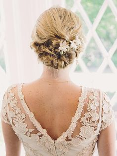 Show off the intricate details on the back of your dress by sporting a braided updo wedding hairstyle paired with white stephanopoulos flowers.