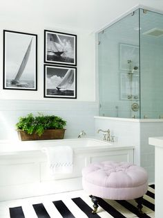 Master bathroom with striped runner, white tub, and glass shower.