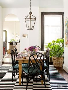 Design aspects such as the striped rug and sleek black chairs play off a humble wood farm table in the room. An oversize wrought-iron chandelier stands out against clean white walls; striking black paint highlights the architectural details around the windows.