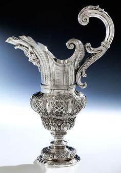 Höhe: 37 cm. Gewicht: 1780 g. Wohl Portugal, um 1700 Silber, getrieben, gegossen, graviert. Gefußte Balusterform mit Bandelwerk und weitem Maskeronausguss und...