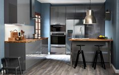 A kitchen with grey high-gloss drawers and doors. Combined with a grey kitchen island and black bar stools
