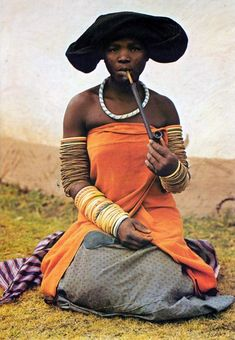 woman in her best dress smoking the typical wooden pipe, Xhosa, South-Africa,