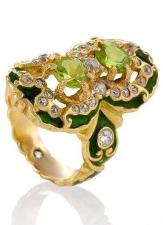 An American Art Nouveau gold, peridot, diamond and enamel ring by Marcus & Co. The unique Renaissance Revival motif features green enamelled 18-karat gold, two round-cut peridots and 30 round-cut diamonds. The Renaissance Revival design influence is carried onto the ring shank culminating in a diamond set shank bottom. Circa 1900. #Marcus #ArtNouveau #ring