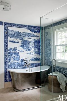 A bath sports a mural by Chelsea Arts Tile + Stone; the tub is by Waterworks, with fittings by Lefroy Brooks | archdigest.com