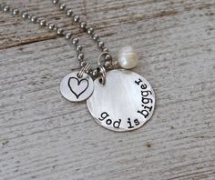 """No matter the situation, God is bigger! He is greater and has it all under control. This necklace is made of two sterling silver discs. The larger one is just under 1"""" from side to side.  They are hand stamped with the words """"God is Bigger"""" and a heart, exclusively designed for The Rusted Chain.  They're paired with a bumpy freshwater pearl and strung on an 18"""" stainless steel ball chain. To care for your stamped jewelry, simply wipe it with a sterling ..."""