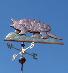 """Snapping Turtle Weather Vane by West Coast Weather Vanes.  This particular turtle weathervane was made with a copper body and shell and brass terrain under its feet. However, because each weathervane is made to individual order, customers can select what combination of metals we use when we make their weather vane. We actually order custom glass eyes to give the """"Snapper"""" a more life like appearance."""