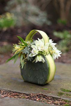 Floral purse with eucalyptus foliage, variegated flax, mini leucadenron, flowering acacia, berzillia, mini cymbidiums, narcissus and succulents, by Floral Verde LLC in Cincinnati, OH.