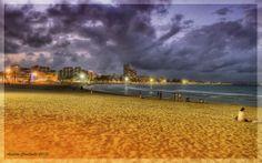 Playa de Peñiscola con edificios iluminados al fondo