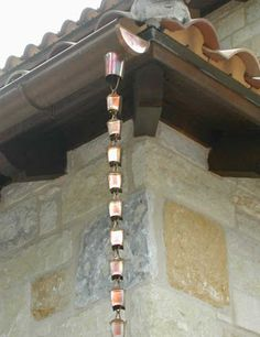 Rain chains are a series of metal cups with holes in the bottom, chained together vertically. The chain moves rainwater from gutters to a drain or a storage Rain Chain Diy, Rain Chains, Rain Catcher, Rain Collection, Lawn Sprinklers, Water Beads, Garden Art, Garden Ideas, Garden Design