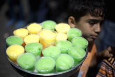 A young Palestinian street vendor carries flavored ice-blended drinks during a…