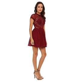 Free People All That Talk Dress Burgundy - SKU 8455817. Gorgeous fit-and-flare dress features sheer lace and pintuck-pleated panels for a striking contrast. Peter pan collar and short sleeves. Nipped waist is figure-flattering. Zip closure at side. Button-loop closure at back. Flared hemline falls at mid-thigh. Lined skirt. 100% cotton; Lining: 100% polyester.