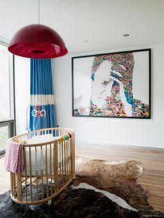 Oversized elements like a domed pendant and modern artwork fill a minimally furnished nursery