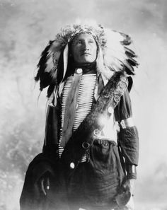 1900 Plenty Holes, a Sioux Indian in feather headress and bone breastpiece.