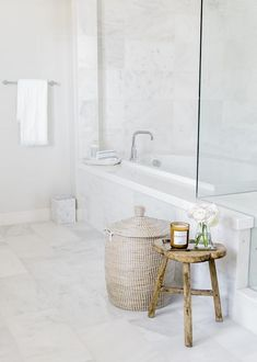 White and gray master bathroom decorated with a woven hamper and a rustic wooden stool beside a marble-tiled drop in bathtub. Marble Tile Bathroom, White Marble Bathrooms, Bathroom Spa, Bathroom Floor Tiles, Bathroom Ideas, Chair In Bathroom, White Master Bathroom, Bathroom Renovations, Rustic Stools