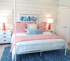 Fresh cheerful bedroom idea in blue with some pink! The white poster bed gives the space a great modern vibe. It's lovely, somewhat minimal. A beautiful coastal beach bedroom, featured on Completely Coastal.