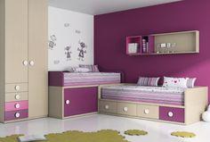 Este es el otro dormitorio. Hay dos camas muy cariñosas, algunos cajones donde poner la ropa, una pequeña librería, y un grande armario. La pared es de color violeta. Hay también una alfombra verde. Es un dormitorio muy íntimo y colorado.