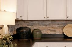 When staging, kitchen counters should be free of clutter and showcase any design or architectural element that make the space a selling point for a potential buyer. This beautiful, stone backsplash is accented by carefully selected antiques, not overshadowed by normal kitchen clutter. #kitchen #interiordesign #staging #kellycruzinteriors