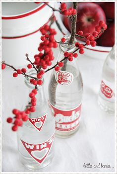 vintage bottles . . .with red berries . . .would be cute is mason jars as well!
