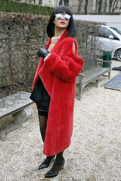 Rihanna stuns in a bright red Dior coat and silk black dress at the fashion house's F/W 14 runway show.