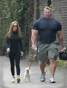 Funny Dog with Big Muscular Guy- big guy is walking with his cute small pet - a Pomeranian dog.