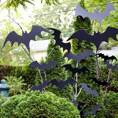 Flying Bat Display from bhg.com  enlarge bat pattern. Cut out on black foam core board. Punch 2 holes in each bat. Adhere to tree branches with black cable ties, tightly.