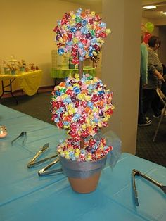 I want to do these...so easy! these candy topiaries using a foam form and mini lolipops. Just cut them off and stuck them in the foam. Then put in a pot and tied ribbon around them. So cute. We used them as the centerpieces on the serving tables.