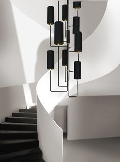 Grande Vortex Chandelier, a custom stairwell chandelier design by Martin Huxford. The arrangement of the asymmetric arms and column shaped upright shades creates a large statement modern staircase light fitting. Made in England.