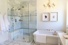 interior design and furnishings by alice lane home collection and caitlin creer | master bath, carrera marble, crystal artwork, glass chandelier, freestanding tub, white towels, white bathmat