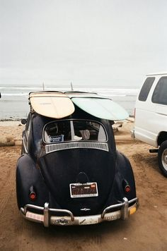 Vintage VW Volkswagen bus buggy with pastel pink and blue surfboards on the beach ocean sea sand of Hawaii California beach island paradise in summer