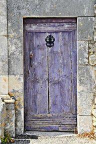 Faded light purple paint on a wooden door