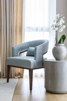 A custom made armchair with curvaceous art deco shape, covered in textured pale blue silk sits alongside a shagreen stool and large Asian vase creating a refined vignette in a contemporary London apartment.  Interiors by boutique design studio- Anouska Tamony Designs