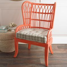 Coral Red Rattan Wing Back Chairs Layered Coral finish is applied to this rattan wing back arm chair that is extremely comfortable and is sure to catch your attention. Combined with a beige linen seat cushion that is upholstered in a very handsome tufted box style. Set of two.