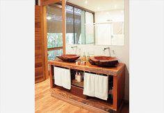 Para levar a natureza para dentro do banheiro de 7 m² , a arquiteta Ana Karina Abud projetou o boxe com revestimento de seixos telados na cor areia. As duas pias ficam sobre a bancada de madeira teca