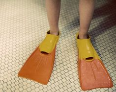 swimmer - child with red and yellow flippers standing on a tiled floor dripping wet Fine Art Print