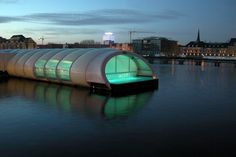 """The Badeschiff. Berlin, Germany. Badeschiff or """"bathing ship"""" is the most unusual swimming pool in Berlin. It is an old cargo container converted into a pool on Spree River. During the summer it is an outdoor pool with the beach, bar and DJs. In the winter the whole thing is covered."""