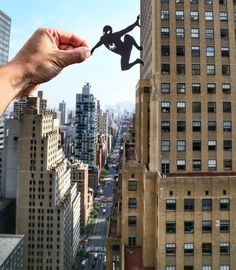 A paper Spider Man is climbing the building in New York.  Rich McCor aka Paperboy