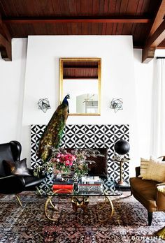Living room with printed fireplace, a camel leather love seat, and a large gold mirror