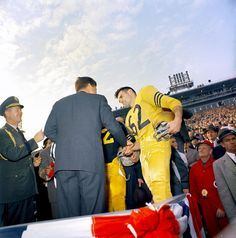 Kennedy shaking hands with the captains of the Army and Navy football teams.