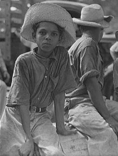 Un agricultor y su hijo montado en la parte posterior de una camioneta en camino al trabajo en una finca de San Sebastián, Puerto Rico (1942)