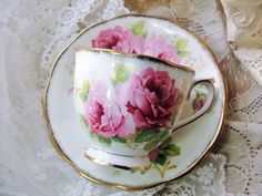 Beautiful vintage English bone china teacup and saucer. This is a lavish set that is colorful and elegant with lush PINK ROSES flowers, adorned with rich abundant gold trim. The cup and saucer are by