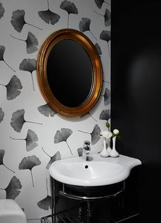 A gold leaf oval mirror is mounted to Ginkgo Marimekko Wallpaper above a  curved sink placed d06402a16a